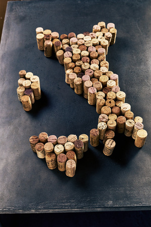 Shape of Italy made of wine corks arranged on dark table