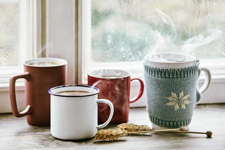Quatre tasses chaudes de thé fumant sur un rebord de fenêtre lumineux du matin. Banque d'images - 83301155