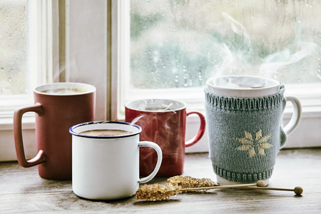Four steaming hot cups of tea brewing on a bright morning window sill. Archivio Fotografico