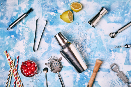 Collection of Cocktail Bar utensils scattered on blue background with lemon and bowl of cherries