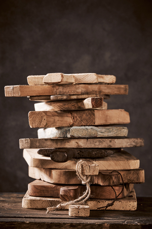 Stack of old and vintage wooden cutting boards piled high on a wooden table in a close up view over a dark background with copy space