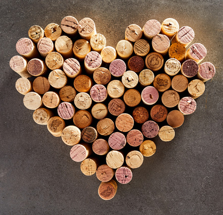 Wine corks arranged into shape of heart against dark background