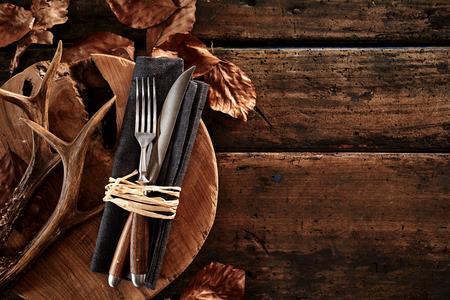 Hirschgeweihe mit Besteck auf Holzbrett gegen Tisch angeordnet Standard-Bild - 83301351