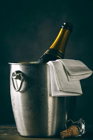 Open bottle of champagne chilling in metal bucket