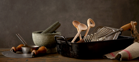 Spoons, mortar with pestle and kitchen utensils on wooden table