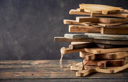 Dozen wooden cutting boards arranged in stack against dark background