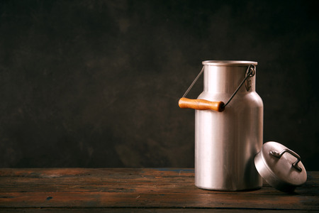 Still life with metal vintage milk can standing on wooden countertop Stock fotó