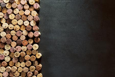 An assortment of authentic, rustic wine bottle corks beside empty black copy space.