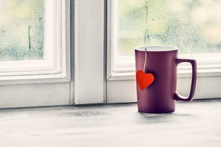 A cup of tea with a red love heart tag brews on a bright morning window sill.