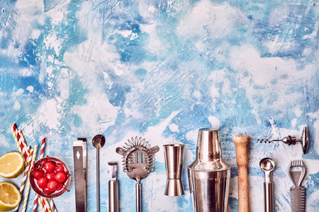Collection of Cocktail Bar utensils arranged in row on blue background