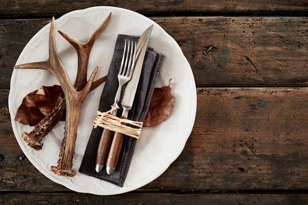 木製のテーブルに対してプレートのカトラリーと鹿の角 写真素材