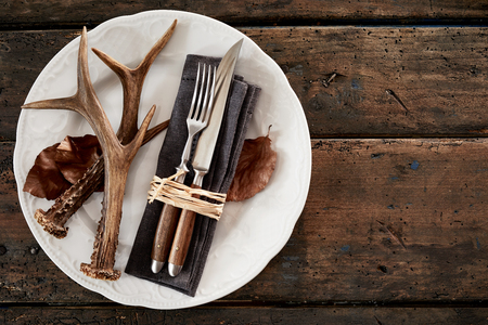 Deer antlers with cutlery on plate against wooden table