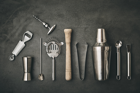 Collection of Cocktail Bar utensils arranged against dark background Stock Photo