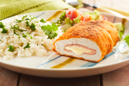 Fired cordon bleu chicken served with rice and parsley on plate Stock fotó