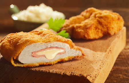 Fried cordon bleu pork served on wooden cutting board 写真素材