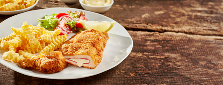 Fried cordon bleu chicken served with french fries and salad on plate against wooden table