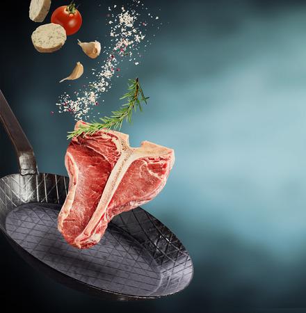 調味料と古いフライパンまたは正方形フォーマットにコピー スペースをフライパンの上に浮かんで調味料の新鮮なハーブと新鮮な健康的な生 t ボー