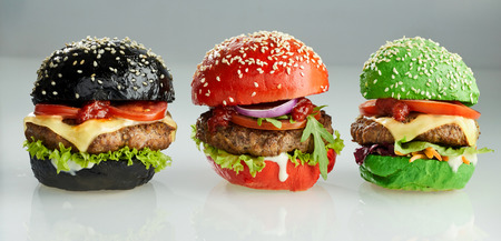 Three Asian burgers with beef patties and salad trimming on colorful red, green and black buns, two with the addition of cheese Фото со стока