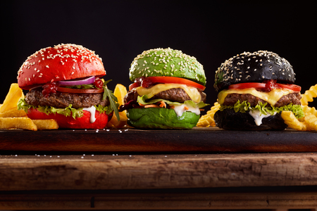 three, hamburgers on colorful bred buns in red , green and black giving assorted options of filling viewed from the side on a wooden board Imagens