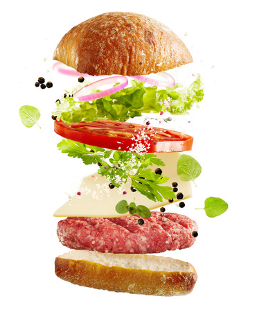 Isolated ingredients for a traditional hamburger floating in air in layers with a crispy bun, fresh salad greens, tomato and onion, cheese, salt, peppercorns and a raw beef patty over white Stock Photo
