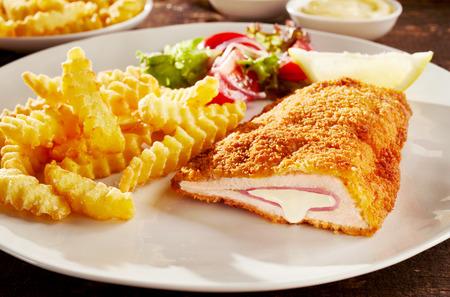 Stuk gebakken cordon bleu kip geserveerd met frietjes en salade op bord