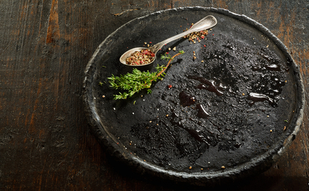 Black empty plate with spoon and spices lying on wooden table Imagens
