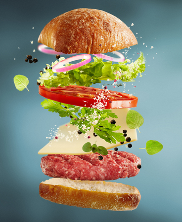 Floating layers of ingredients for a cheeseburger suspended in the air with a bread roll, beef patty, cheese, spices, fresh salad greens, tomato and onion over a graduated grey background