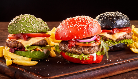 Three colorful Asian beef and cheese burgers with French Fries on red, green and black sesame buns served on a wooden board Archivio Fotografico