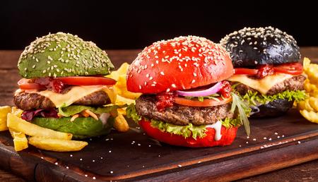 Trois burgers asiatiques colorés au b?uf et au fromage avec des frites sur des petits pains au sésame rouges, verts et noirs servis sur une planche de bois