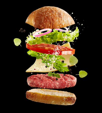 Floating fresh ingredients for a beef burger over a black background with fresh salad greens, bun, condiments , slice of cheese and raw meat patty suspended midair in layers