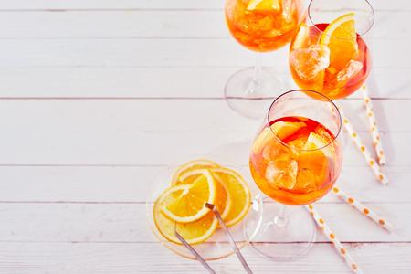 빨 대와 aperol spritz 칵테일을 새로 고침 하 고 흰색 목재 테이블에 오렌지 슬라이스.