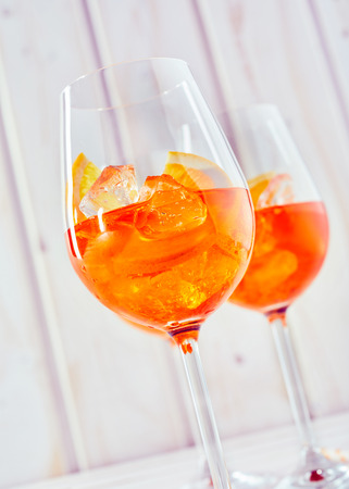 A close up of aperol orange spritz cocktails and glasses with a plain white timber background in vertical portrait orientation.