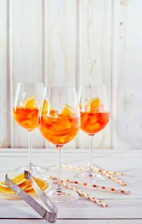 Refreshing aperol spritz cocktails with straws and sliced orange on a white timber table in vertical portrait orientation.