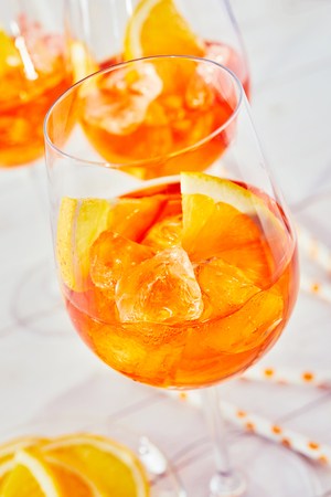 A close up of refreshing aperol orange spritz cocktails and glasses with a plain white timber background.