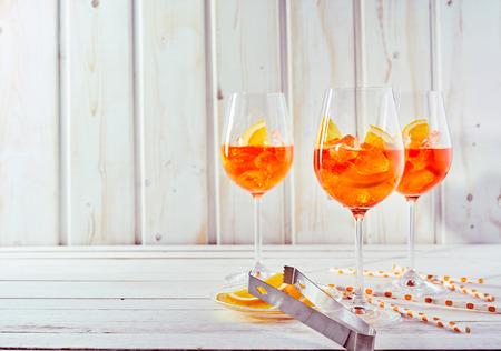 Verfrissende aperol spritz cocktails met rietjes en gesneden sinaasappel op een witte houten tafel.