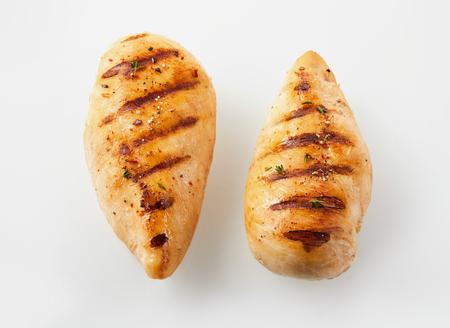 A close up of two golden, grilled chicken breasts with a white background and copy space. Stock Photo