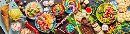 Una variedad de dulces coloridos, festivos, helados y dulces en una orientación panorámica.