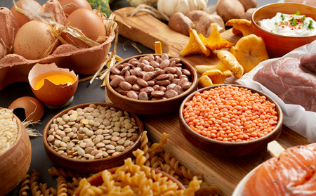 An authentic assortment of healthy legumes, eggs, pasta, mushrooms and meat on a rustic table setting with a wooden chopping board.