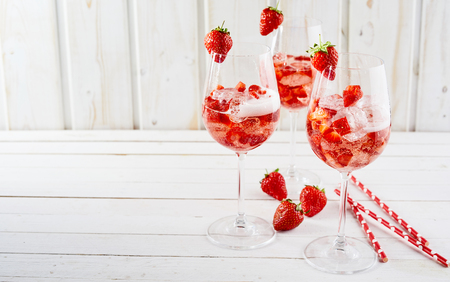 Strawberry cocktails with and without alcohol served on crushed ice in wine glasses as a refreshing aperitif over rustic white wood with copy space Stok Fotoğraf