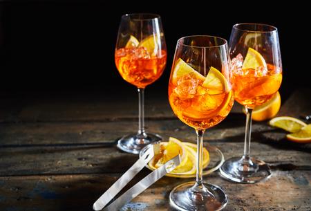 Refreshing lemon, citrus spritz cocktails on rustic, dark timber background with sliced lemon.