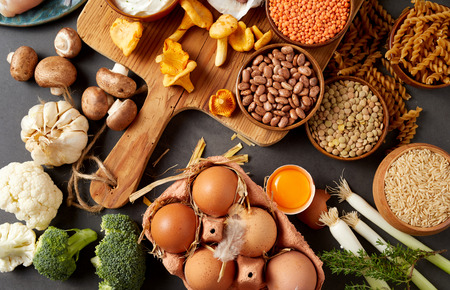 An authentic assortment of healthy, organic legumes, eggs, pasta, mushrooms and meat on a rustic table setting with a wooden chopping board. Stock fotó