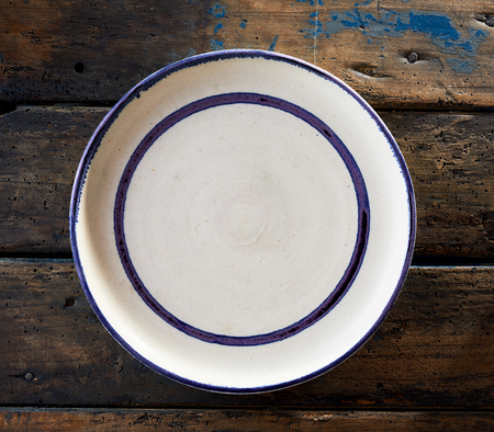 Empty clean white ceramic plate with blue rim and border viewed from overhead on rustic wood in square format Zdjęcie Seryjne