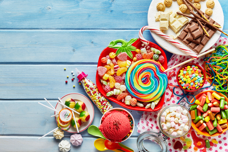 Overhead view of colorful array of different childs sweets and treats in bowls on light blue wood background Banco de Imagens