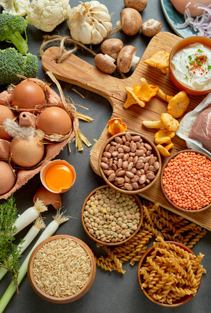 An authentic assortment of healthy, organic legumes, eggs, pasta, mushrooms and meat on a rustic table setting with a wooden chopping board in vertical portrait orientation. Stock Photo