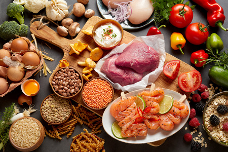 A rustic assortment of paleo foods including, eggs, legumes, vegetables, fish, meat, muesli and pasta on a wooden chopping board with a dark grey background.