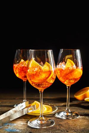 Refreshing lemon spritz cocktails on rustic, dark timber background with sliced lemon.