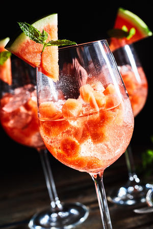 Close up of bubbly, refreshing watermelon, mint cocktail beverages with a dark, black background. Stock Photo
