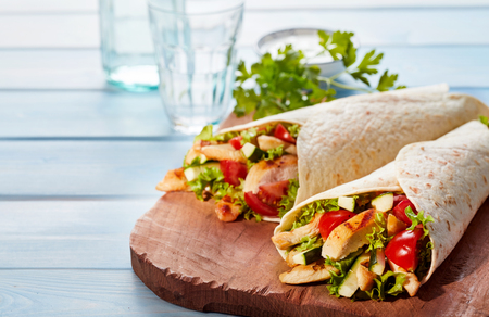Two fresh chicken and salad tortilla wraps on wooden cutting board with glasses in background Archivio Fotografico