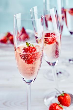 Rosafarbener Champagner mit frischen, reifen Erdbeeren serviert in einer hohen eleganten Flöte für einen besonderen romantischen Anlass oder Aperitif