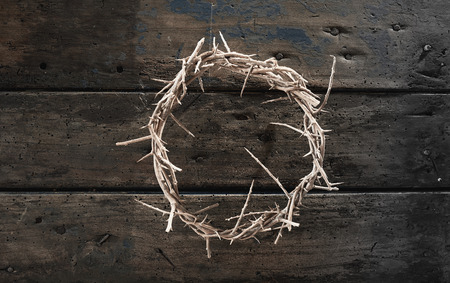 Circlet or crown of thorns on rustic wood symbolic of the crucifixion of Christ at Easter viewed from above